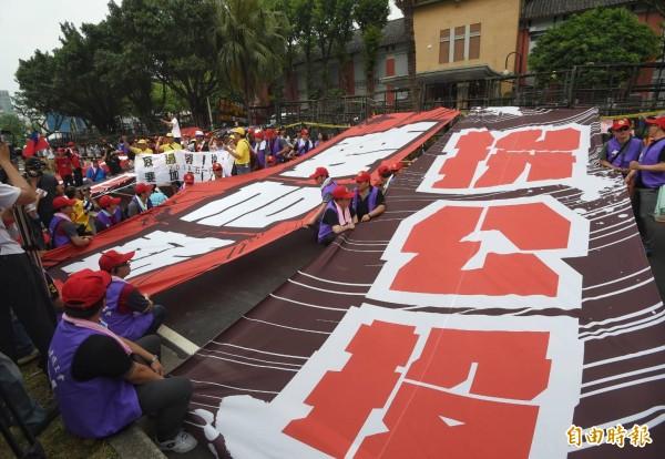 「五一行動聯盟」發起勞工大遊行,在遊行終點立法院綁「拚公投」等大型標語表達訴求。(記者方賓照攝)