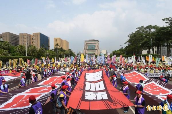要加薪!「五一行動聯盟」發起勞工大遊行,在遊行終點立法院綁大型標語表達訴求。(記者方賓照攝)