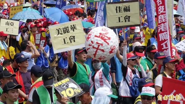 「五一行動聯盟」1日發起「勞工大遊行」,參加勞工舉標語表達訴求。(記者方賓照攝)