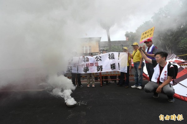 勞工在遊行終點立法院燒狼煙宣誓決心。(記者方賓照攝)
