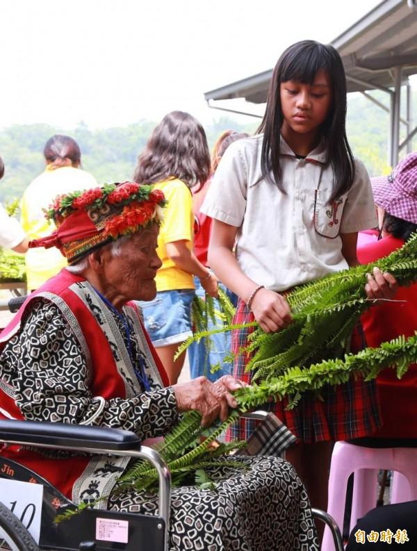 老幼共同利用植物編織頭飾。(記者羅欣貞攝)