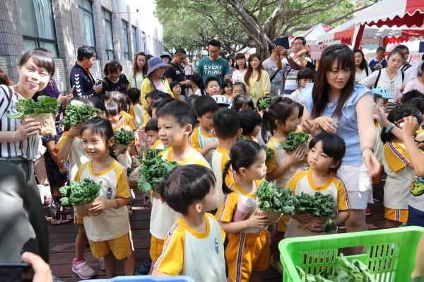 小朋友當農夫市集的小店長,拿著自己種的蔬菜販賣。(記者蔡淑媛翻攝)