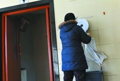 一名中年女子在公廁內專等沒人時抽走一大段衛生紙,這行為在半小時內重複了3次。(圖擷自《北京晚報》)