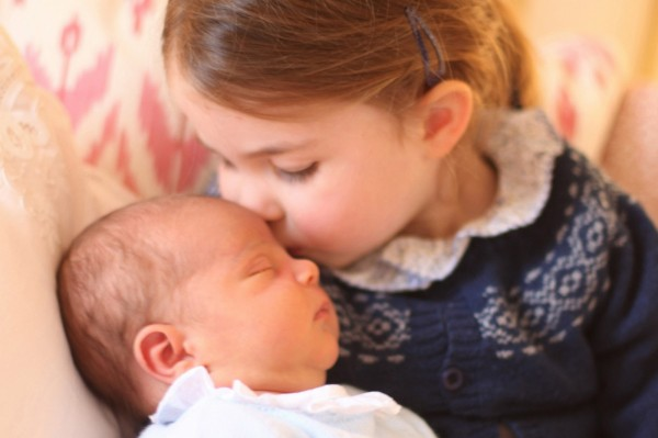 英國皇室夏綠蒂公主(Princess Charlotte),溫柔地親著弟弟路易小王子的額頭。(路透)