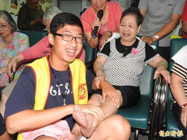 70歲的謝惜阿嬤讓男同學洗腳與乳液按摩,直呼「金拍謝!」(記者佟振國攝)