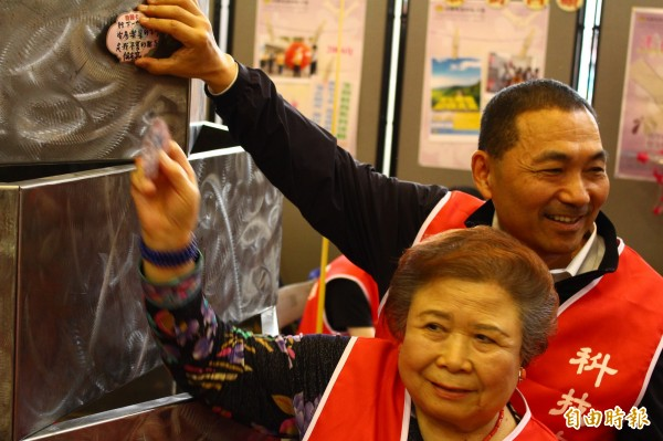 侯友宜(上)與宏國德霖技術學院董事長林謝罕見一同將心願卡貼在許願樹上。(記者邱書昱攝)