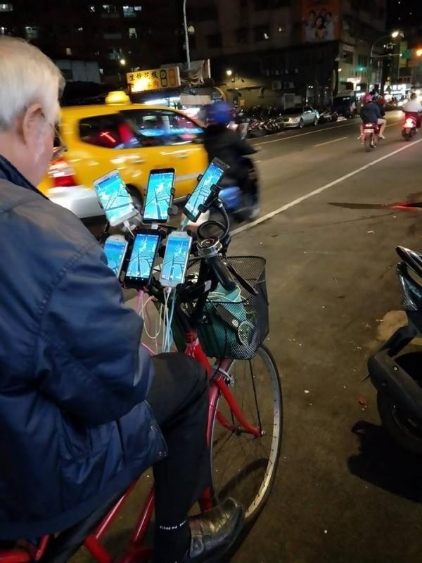 阿伯在腳踏車上裝了6支手機同時抓寶,被外國人封為「鐵血玩家」。(圖擷取自爆廢公社)