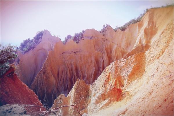 像被鋸齒削過的山峰立面極富氣勢,加上礫質惡地與裸露的紅土台地,造就火炎山的經典景觀。(記者李惠洲/攝影)