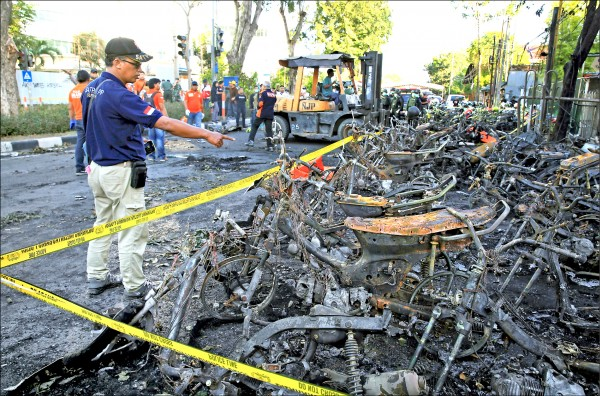 印尼泗水三座教堂十三日遭連環自殺炸彈攻擊,中央聖靈降臨教派教堂外的成排機車遭波及陷入火海,火勢撲滅後燒成廢鐵。(路透)