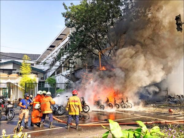 印尼泗水三座教堂十三日遭連環自殺炸彈攻擊,造成包括自殺炸彈客在內至少十三人死亡,消防人員忙著撲滅泗水中央聖靈降臨教派教堂的火勢。(路透)