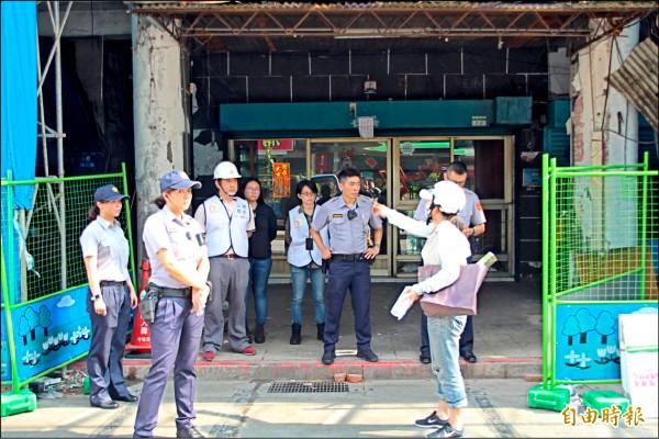 不同意戶昨下午到現場時,市府人員與警衛組成人牆拒絕居民進入,不同意戶對內大罵。(記者鍾泓良攝)