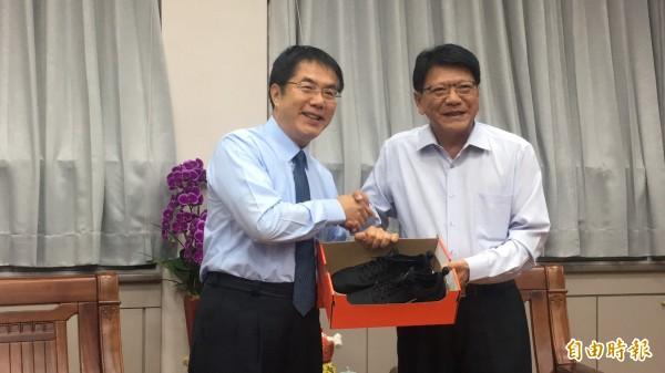 潘孟安準備了一雙球鞋給黃暐哲,勉勵「黃市長」勤跑基層。(記者邱芷柔攝)