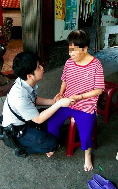 警方帶著迷路老婦到一旁信安宮陰涼處休息,輕聲安撫。(記者王宣晴翻攝)