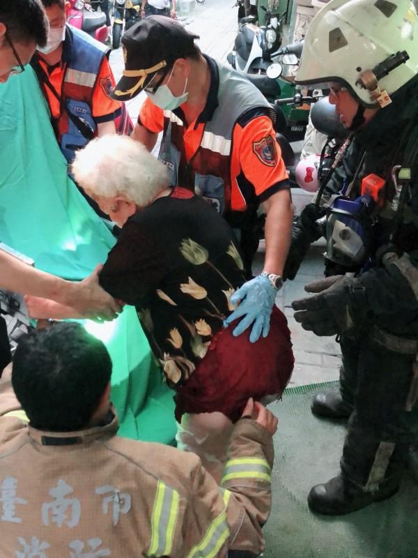 消防員協助遭氣爆灼傷的八旬老婦送醫。(記者王俊忠翻攝)