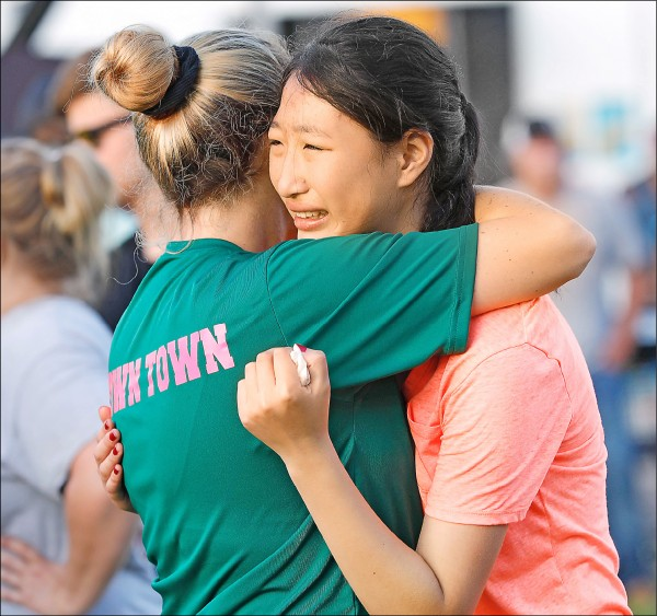德州小城聖塔菲十八日發生校園血案,當地社區舉行燭光晚會,為逝者默哀、祈禱並唱聖歌,死傷者親友相擁而泣。(法新社)