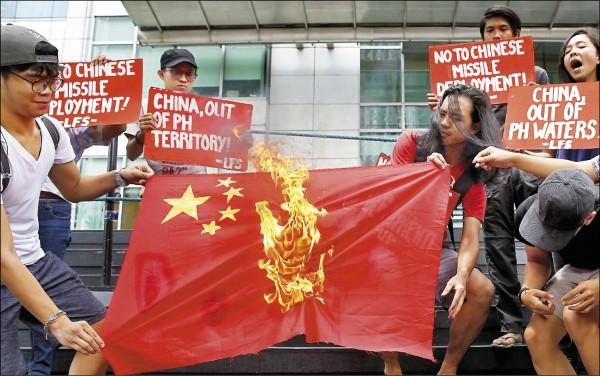 菲律賓民眾十日在首都馬尼拉衛星城市馬卡蒂(Makati)的中國領事館前焚燒中國五星旗,抗議中國在南海島礁部署防空及反艦飛彈。(美聯社)