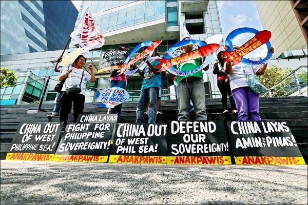 菲律賓抗議者十八日在馬卡蒂中國領事館前,高舉寫有捍衛南海領土主權、要求中國離開的標語示威。(歐新社)