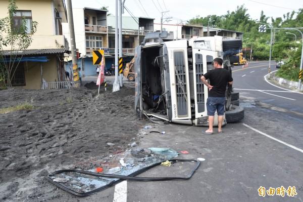 砂石車疑似爆胎失控翻車,差點撞入一旁民宅。(記者蘇福男攝)