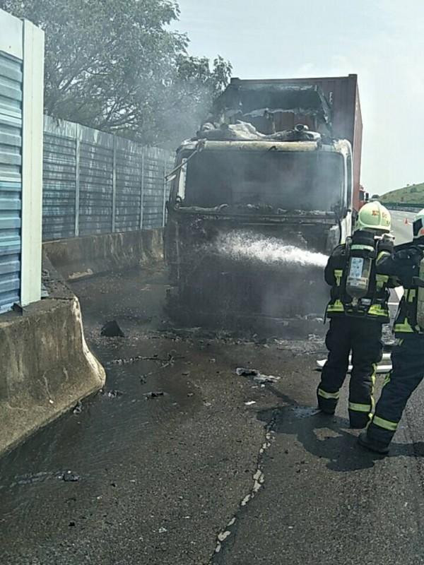 消防人員朝貨櫃車噴水灌救,整輛車頭燒成廢鐵。(記者湯世名翻攝)