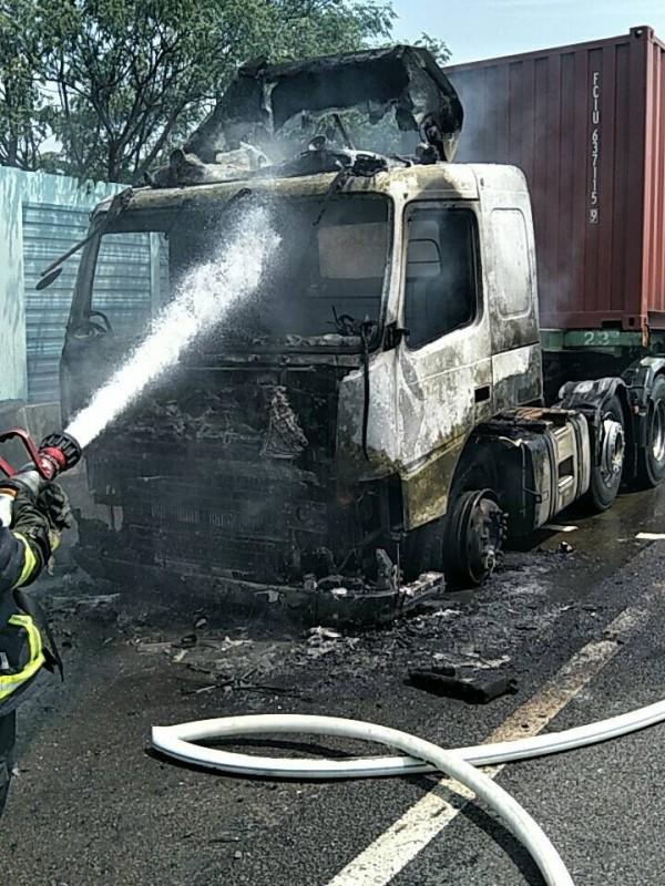 消防人員朝貨櫃車噴水灌救,整輛車頭燒成廢鐵,怵目驚心。(記者湯世名翻攝)