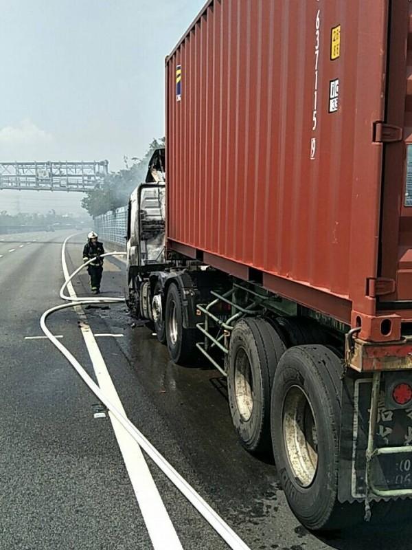 消防人員朝貨櫃車噴水灌救,整輛車頭燒成廢鐵,貨櫃並未受損。(記者湯世名翻攝)