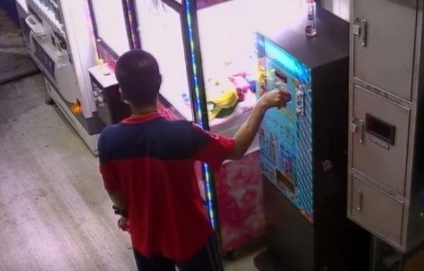 孫男將電擊器插入兌幣機台,干擾兌幣機的運作,讓兌幣機主動掉下錢來。(記者歐素美翻攝)