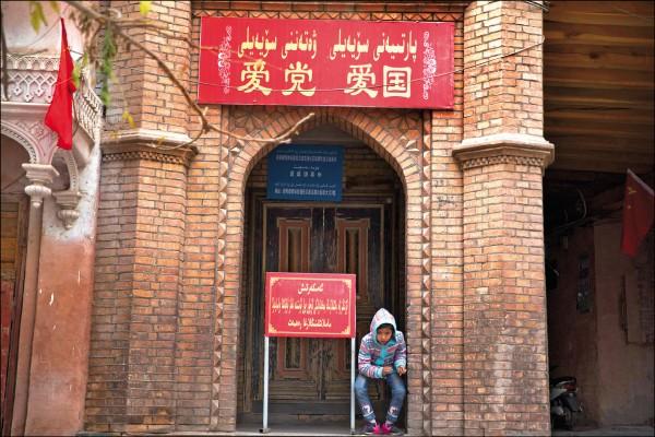 附屬於中國政府的「中國伊斯蘭協會」近日展開要求所有清真寺懸掛國旗、學習憲法等「四進清真寺」活動,提倡愛國愛黨精神。圖為新疆喀什一座清真寺入口掛著寫有「愛黨愛國」標語牌。(美聯社檔案照)