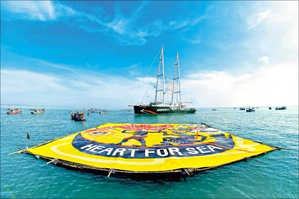 綠色和平組織21日在泰國宋卡府附近的泰國灣,動員大批船隻環繞其環保旗艦「彩虹勇士號」,以及一幅長寬均約30公尺的浮動旗幟,抗議宋卡府計畫興建火力發電廠。(歐新社)