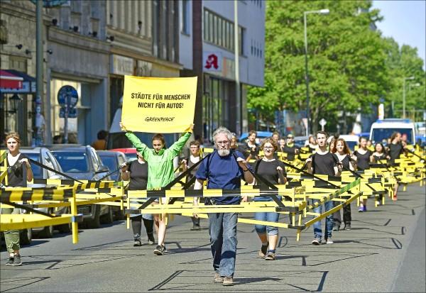 綠色和平組織人士22日在德國首都柏林的十字山區(Kreuzberg)遊行,高舉寫有「城市是為了人而存在,不是為了汽車!」的標語牌,抗議汽車造成的環境污染。(法新社)
