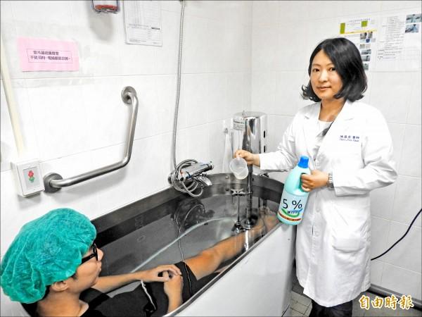 高醫主治醫師陳盈君表示,異位性皮膚炎患者可使用含次氯酸鈉5%的漂白劑,並以溫水稀釋千倍,頸部以下浸泡10分鐘,逾6成患者症狀獲改善,但須經醫師正確診斷及教導,否則可能有反效果。(記者方志賢攝)