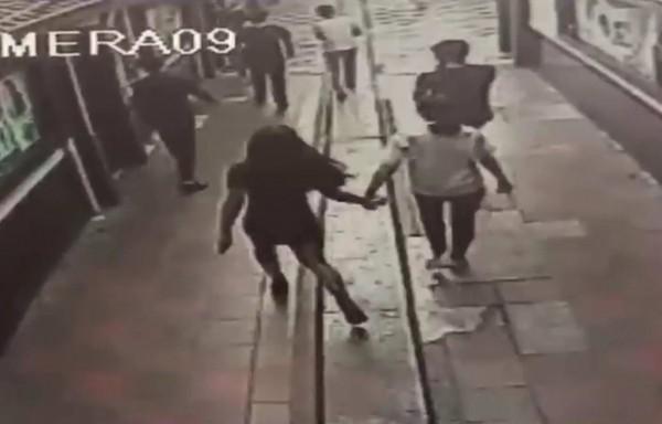 陳姓男子(右側白衣者)與「穿女裝」短裙的男子(左)手牽手走進KTV作樂。(記者湯世名翻攝)