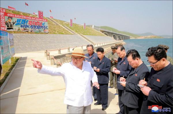 北韓中央通信社廿四日發布一張日期不詳的照片,顯示其領導人金正恩(左一)在東部的江原道視察一座新建成的跨海鐵路大橋,隨行的黨、官媒記者低頭猛抄筆記。(路透)