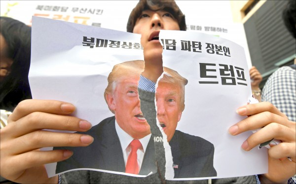 美國總統川普廿四日突片面取消原定六月十二日舉行的美、朝峰會,廿五日在美國駐首爾大使館附近,一名南韓抗議人士把印有川普肖像的圖片撕成兩半,海報上寫著「川金會破局的禍首川普」。(法新社)