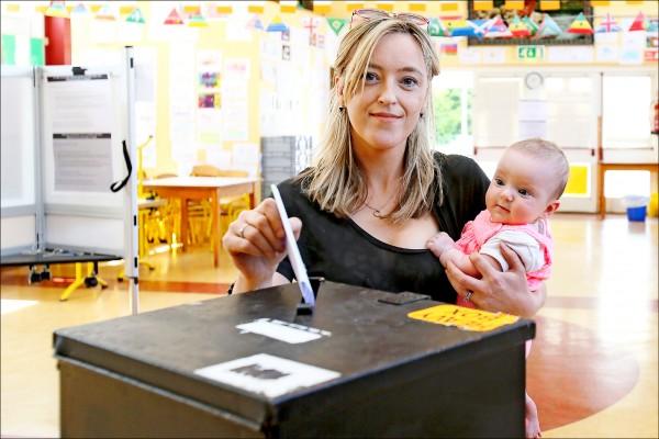 愛爾蘭二十五日針對是否廢除嚴禁墮胎的憲法條款舉行公投,圖為一名婦女抱著五個月大女兒投票。(法新社)