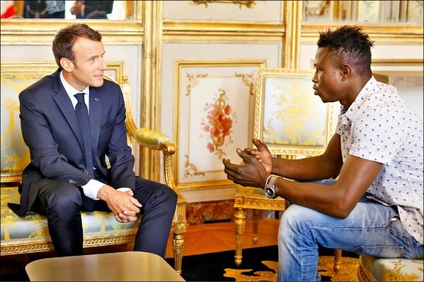 法國總統馬克宏(左)二十八日邀請賈薩瑪至艾麗榭宮,宣布賦予他歸化公民身分加以表揚,並提供他消防單位工作機會。(歐新社)