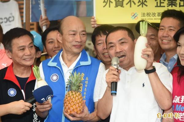 國民黨新北市長參選人侯友宜與高雄市長參選人韓國瑜,今天上午首度在高雄國民市場合體造勢,並促銷農特產品香蕉、鳳梨等,及向市場街坊鄰居拜票。(記者張忠義攝)
