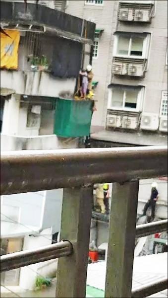 93歲花姓阿嬤從4樓頂抓水管垂降受困,消防人員將她抱進陽台內。(記者林嘉東翻攝)