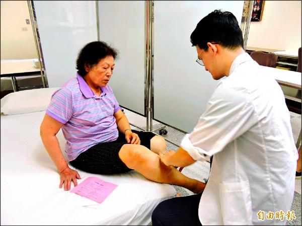 醫師蘇偉翔細心問診,了解民眾的疼痛源。(記者張存薇攝)