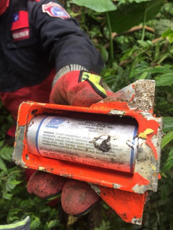 搜救人員拆下黑盒子上的電池拍照供軍方人員辨認。(記者吳昇儒翻攝)