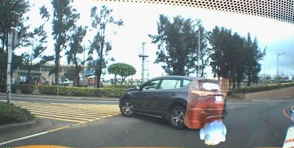 鏡頭前方1輛黑色豐田休旅車,駛入通往南崁、竹圍的右轉道後驟然煞車停住,接著未打左轉方向燈就逕自跨越槽化線左轉。(圖擷取自爆料公社)
