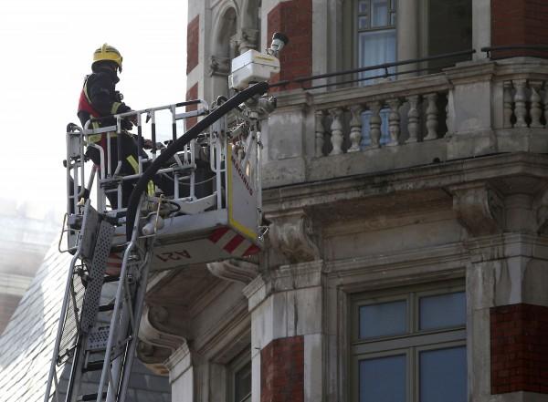 消防隊員為滅火站上雲梯頂端。(路透)