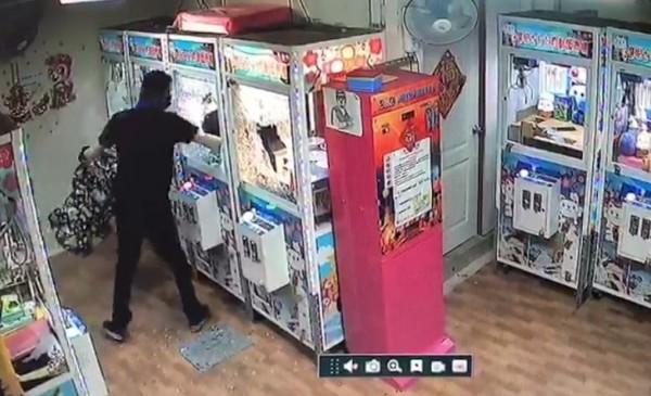 另一名黑衣男將手伸進夾娃娃機台內竊取藍芽音響。(記者歐素美翻攝)
