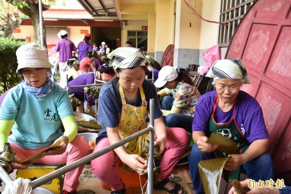林姓阿嬤(右)當志工包粽,國二孫女也來幫忙順便學怎麼包粽。(記者黃淑莉攝)