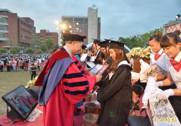 洗腳禮之後,畢業生代表獲贈榮譽狀。(記者吳俊鋒攝)