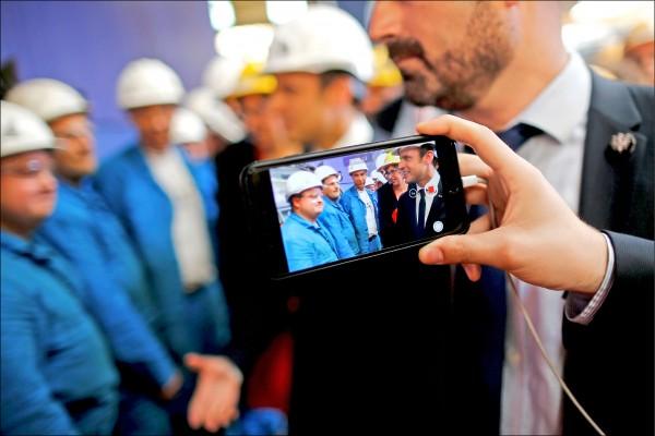 法國國民議會落實總統馬克宏政見,在七日通過法案,禁止公立中、小學孩童在校園內使用手機。圖為民眾以手機拍攝馬克宏五月三十一日訪問聖納澤爾一座造船廠。(路透)