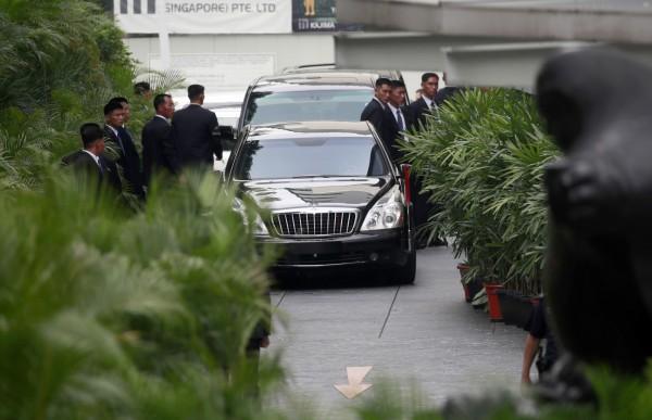 金正恩抵達新加坡後,座車被保鑣團團包圍,重現文金會時保鑣繞著車子跑步的場景。(歐新社)