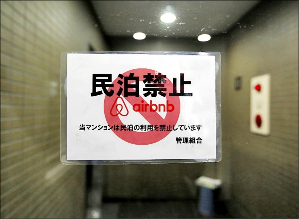 日本民泊新法十五日上路,對短租民宅業是福是禍還是未知數。圖為東京一棟公寓大樓門口張貼的禁止經營民泊的告示。(路透檔案照)
