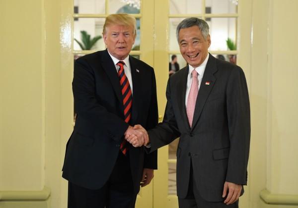 美國總統川普和新加坡總理李顯龍握手後共進午餐。(法新社)