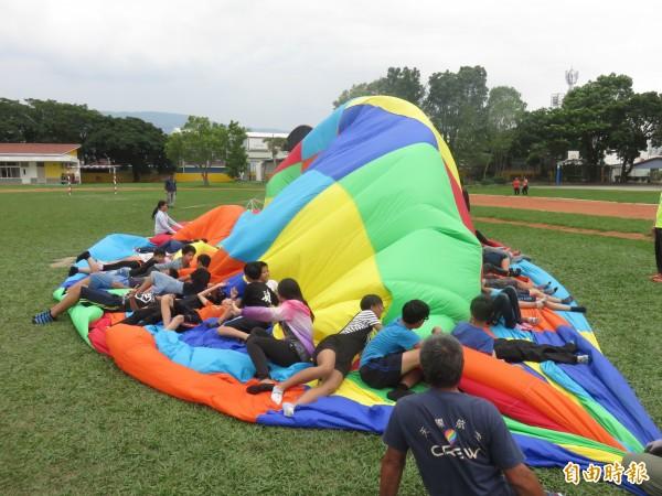 福原國小畢業生跟著飛行員一起學習如何收熱氣球。(記者王秀亭攝)