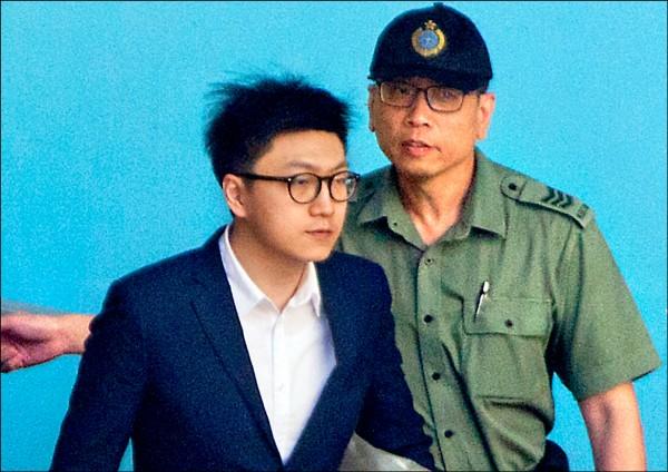 梁天琦(左)因「暴動罪」被收押,十一日在警方押送下赴高等法院聆聽判決。(歐新社)